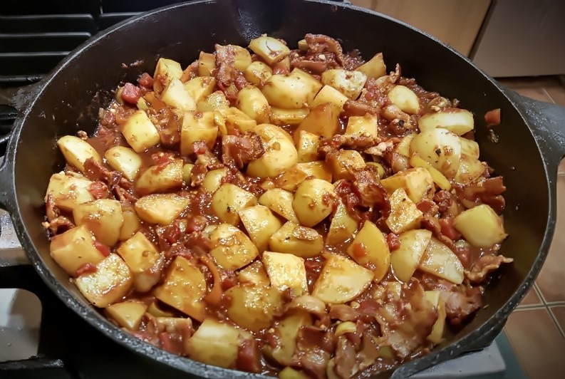Spanish potatoes with bacon and capers in cast iron skillet