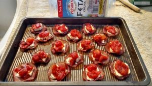 Canadian bacon feta cheese and tomato snacks on a baking tray snacks