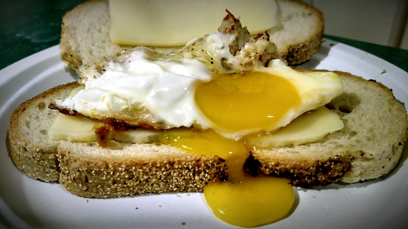 Breakfast fried egg sandwich on rye toast and Swiss cheese on a plate