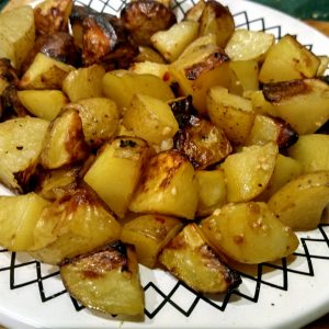 Garlic roasted potatoes on a plate perfect snack for bringe watching TV